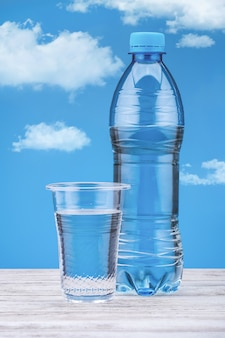 白いテーブルと雲と青い背景に水とボトル。プラスチックカップの真水