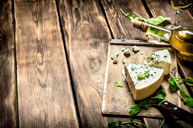 Bottle with white wine and blue cheese on a cutting board.