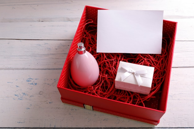 Bottle of woman perfume. red packaging of present.
