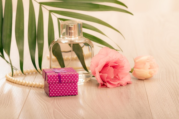 Bottle of woman perfume with beads on a string, flowers and green leaves on pink background. holiday concept