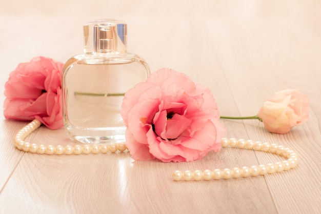 Bottle of woman perfume with beads on a string and flowers on pink background. holiday concept