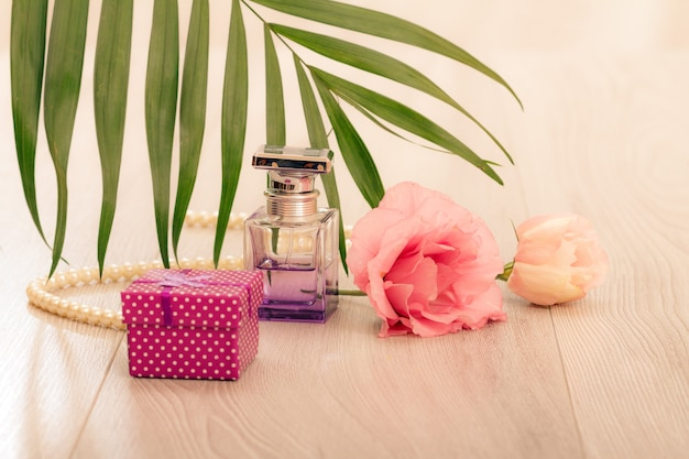 Bottle of woman perfume with gift box, beads on a string, flowers and green leaves on pink background. holiday concept