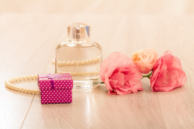Bottle of woman perfume with gift box, beads on a string and flowers on pink background. holiday concept.