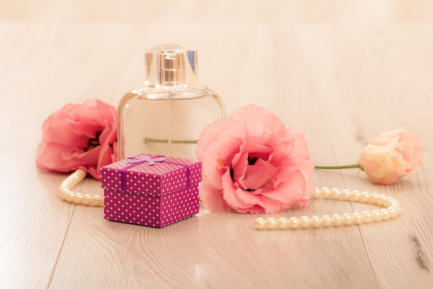Bottle of woman perfume with gift box and flowers on pink background. holiday concept