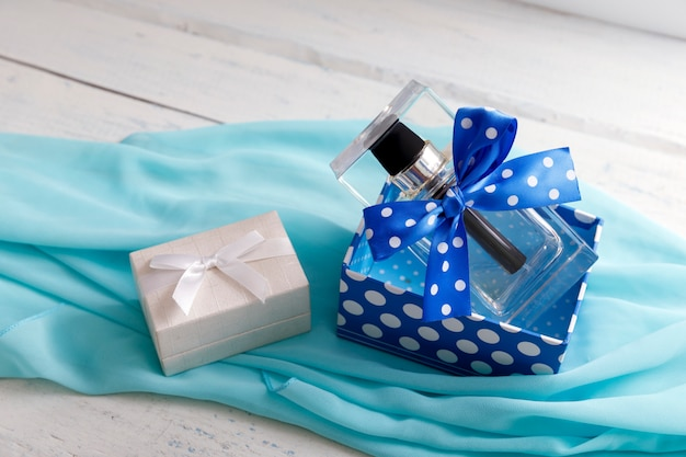 Bottle of woman perfume with white gift box.