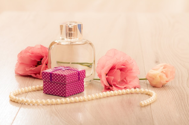 Bottle of women perfume with gift box, beads on a string and flowers on pink background. holiday concept.