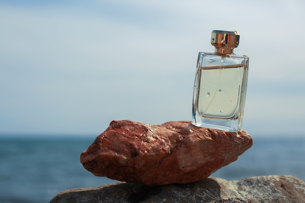 Bottle of women's perfume on the background of the sea