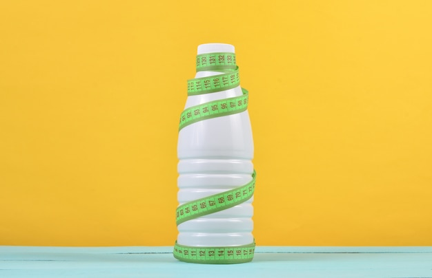 Bottle of yogurt wrapped in a ruler on a yellow background, dietary, slimming concept