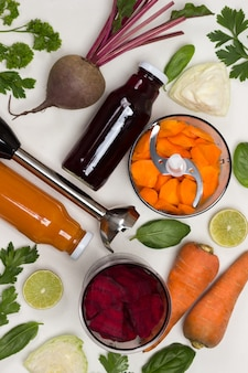 Бутилированный свекольный и морковный соки. корнеплоды свеклы и моркови. нарезанные морковь и свекла в блендере. резак. капуста и зелень. белый фон. плоская планировка