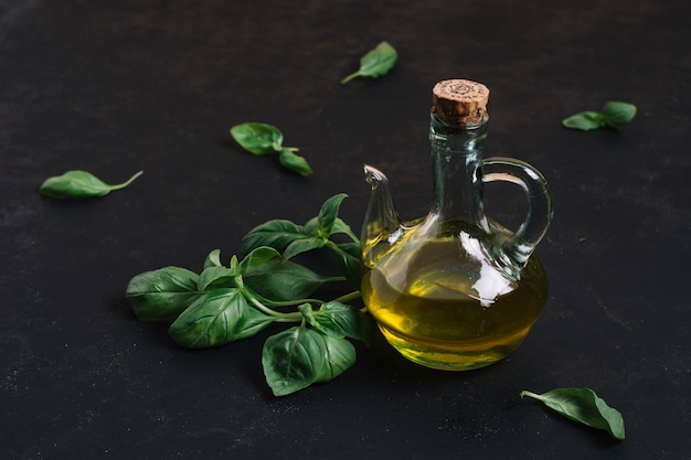 Bottled olive oil with spinach around it