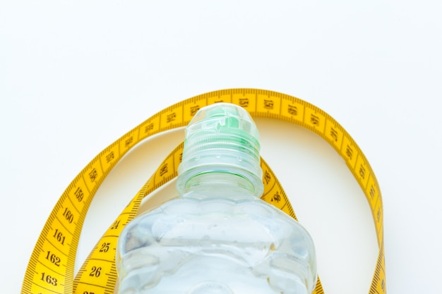 Bottled water for healthy life and measuring tape over a white