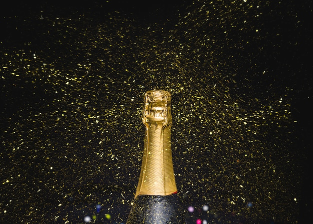 Bottleneck of champagne with flying glitters