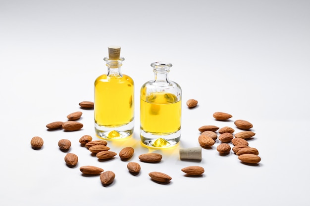 Bottles of almond oil and almonds  on white background, copyspace.