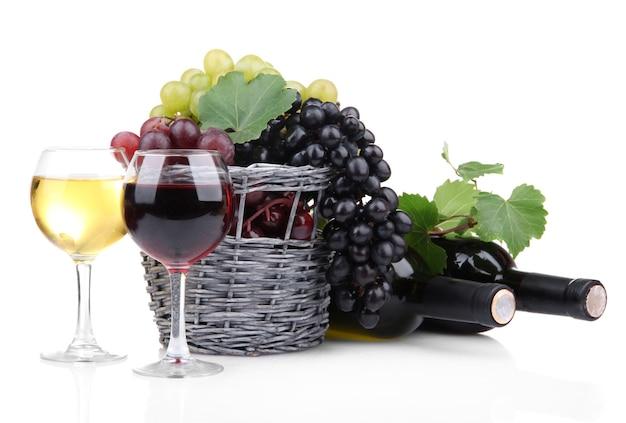 白で隔離のバスケットのワインとブドウのボトルとグラス