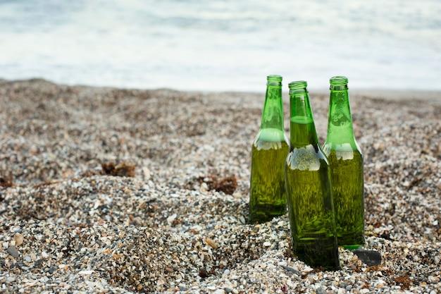 Bottiglie di birra all'aperto nella sabbia della spiaggia con spazio copia