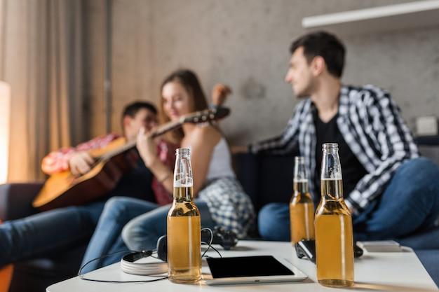 Bottiglie di birra sul tavolo e giovani felici che si divertono sullo sfondo, amici fanno festa a casa, compagnia hipster insieme, due uomini una donna, suonare la chitarra, uscire