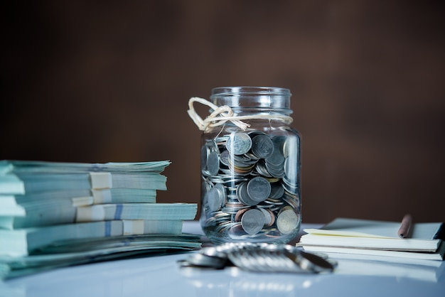 Bottles of cash with coins  in saving money concept