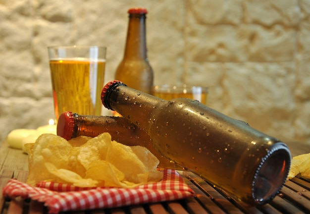Bottles of cold beer and chips on wooden table