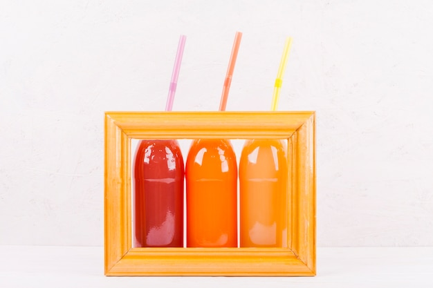 Bottles of colorful juice in frame