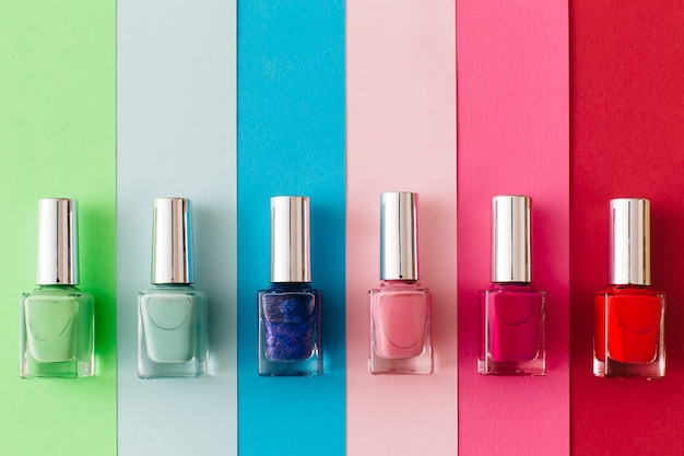 Bottles of colorful nail polish on colorful background. manicure and pedicure concept. flat lay, top view, copy space.