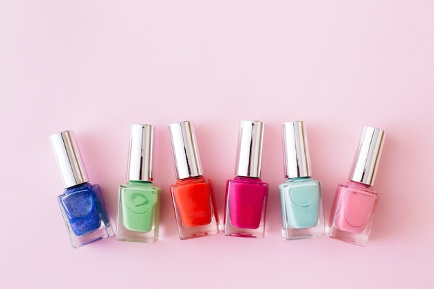 Bottles of colorful nail polish on pastel pink background. manicure and pedicure concept. flat lay, top view, copy space.