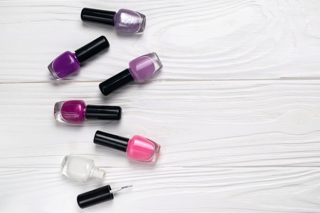 Bottles of colorful nail polish on white wooden background top view with space for text