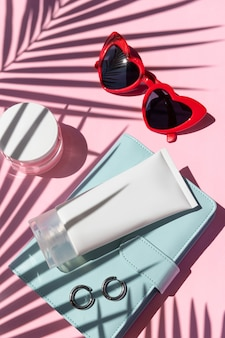 Bottles of cosmetics cream and summer accessories on blue surface