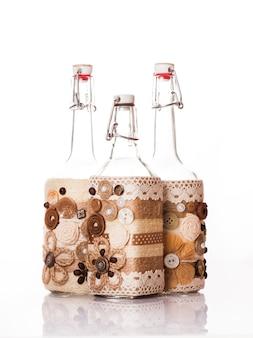 白で隔離のコーヒー豆、シナモン、レースで飾られたボトル