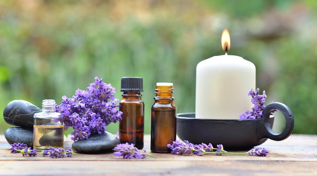 Bottles of essential oil among lavender flower arranged on a wooden table in garden with
