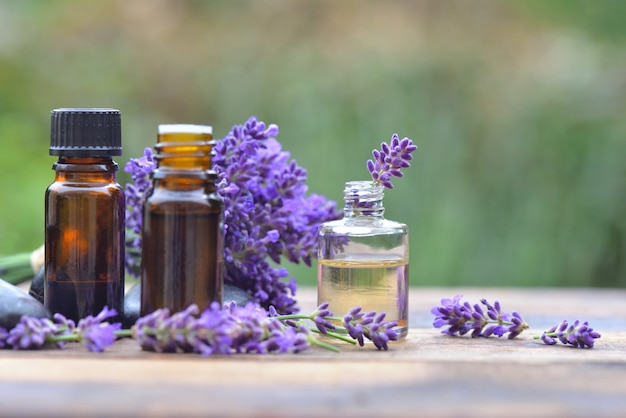 Bottles of essential oil among lavender flower arranged on a wooden table in garden