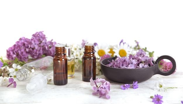 Bottles of essential oil among pink flowers of lilac