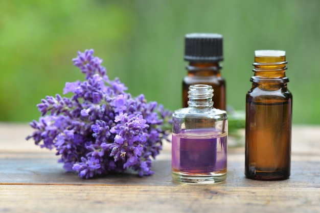 Bottles of essential oil and bouquet of  lavender flower arranged on a wooden table in garden