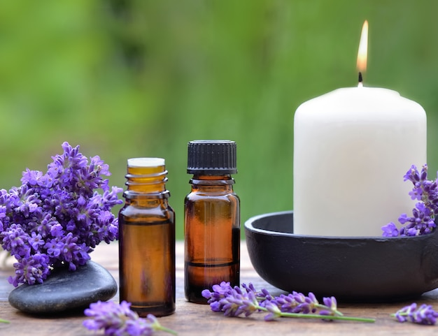 Bottles of essential oil and bouquet of  lavender flower arranged on a wooden table with a candle