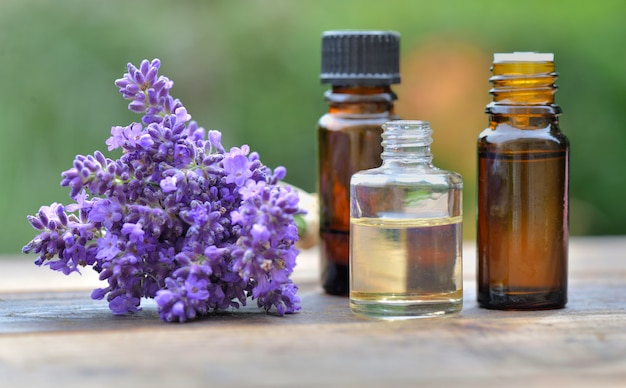 Bottles of essential oil and bouquet of  lavender flowers arranged on a wooden table in garden