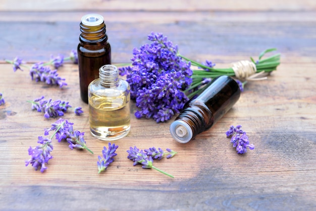 Bottles of essential oil and bouquet of  lavender flowers arranged on a wooden table