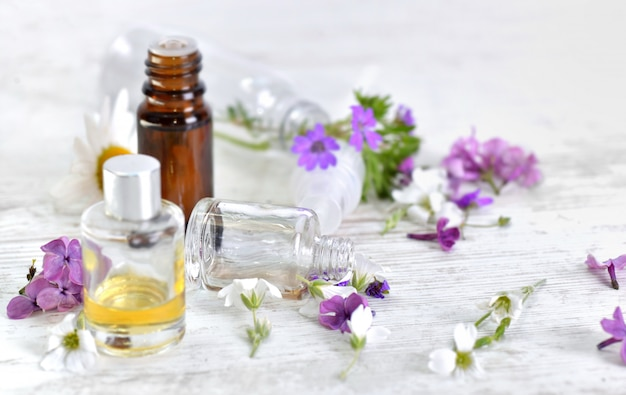 Bottles of essential oil and colorful petals of flowers on white table