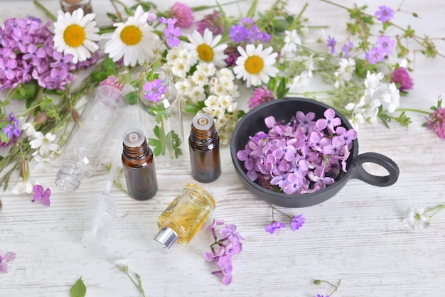 Bottles of essential oil and colorful petals of fresh wild  flowers on white table