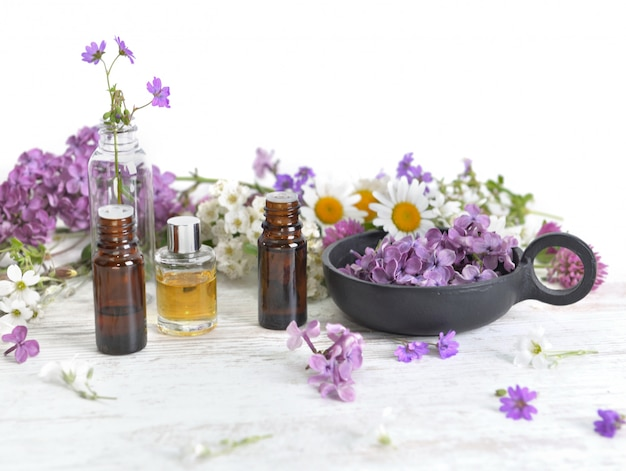 Bottles of essential oil and colorful petals of freshness flowers on white table