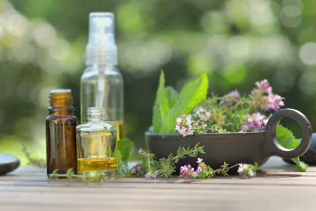 Bottles of essential oil and flowers of aromatic herb on a table