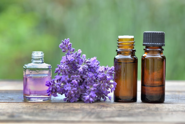 Bottles of essential oil and ouquet of lavender flower arranged on a wooden table in garden