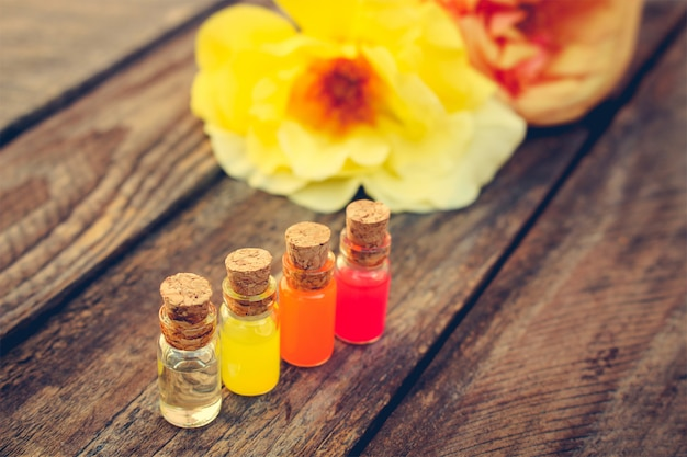 Bottles of essential oil and roses on old wooden .