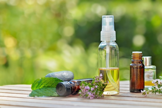 Bottles of essential oil on a table in garden with aromatic plant