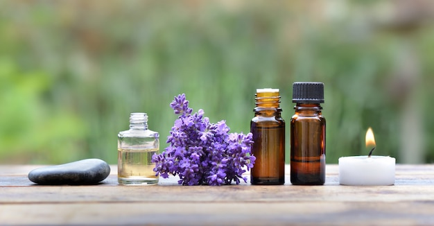 Bottles of essential oil with lavender flower arranged on a wooden table in garden with candle