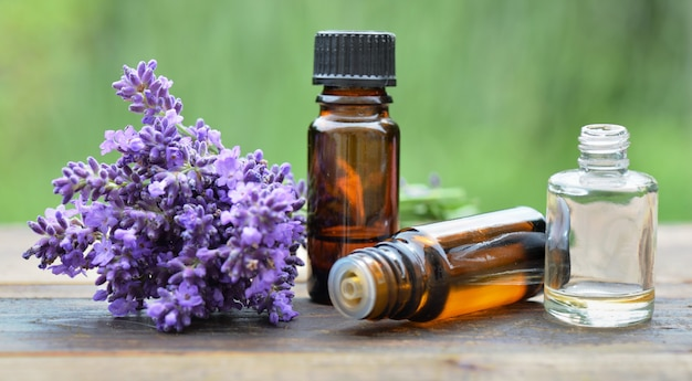 Bottles of essential oil with one spilled on a table and bouquet of  lavender flowers