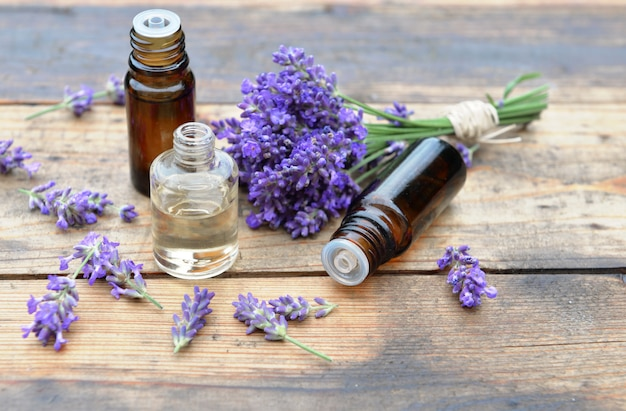Bottles of essential oil with one spilled on wooden background and bouquet of  lavender flowers