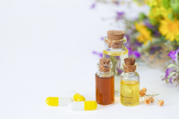 Bottles of essential oils next to herbal capsules on white