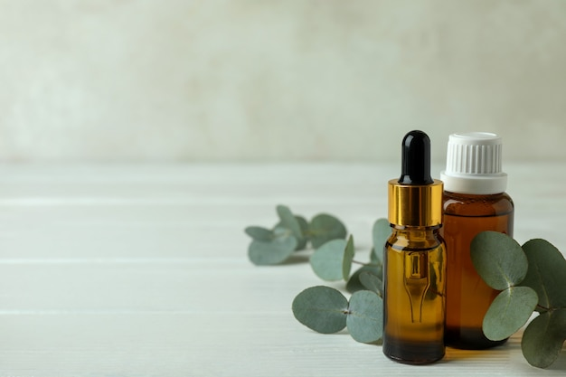 Bottles of eucalyptus oil and twigs on white wooden background