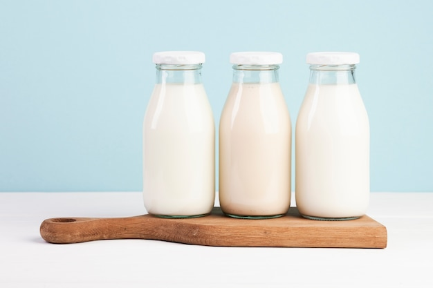 Bottles filled with milk on chopping board