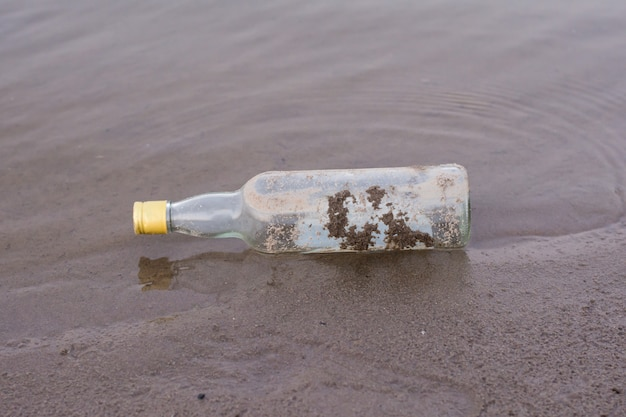 Bottles and garbage waste on the shore of a river.