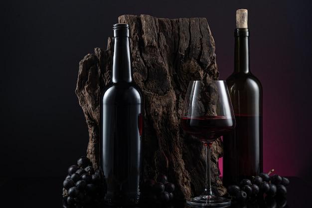 Бутылки, бокал испанского красного вина и виноград на деревянной основе